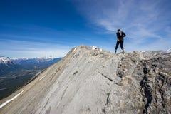 两个人落后跑在加拿大的山的一条陡峭的土坎线 库存照片