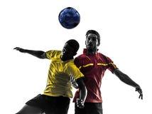 两个人足球运动员战斗的球剪影 免版税图库摄影