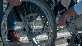 两个人运载一个轮椅的一名妇女在步接近两个人的手的运载一个轮椅的一名妇女在步 股票录像