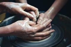 两个人铸造从白色黏土的一个泥罐 库存照片