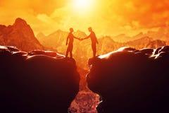 两个人震动移交悬崖 现有量帮助 免版税库存图片