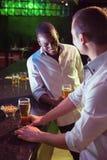 两个人饮用啤酒在酒吧 图库摄影