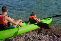 两个人-一个成人和儿童父亲和儿子救生衣的在可膨胀的小船航行在远足期间在夏天 免版税库存图片