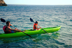 两个人-一个成人和儿童父亲和儿子救生衣的在可膨胀的小船航行在远足期间在夏天 免版税库存照片