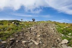 两个人登山人上升到登上山顶  免版税库存照片