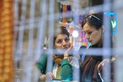 两个伊朗少妇谈话在义卖市场,设拉子里面的商店 库存图片