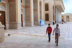 两个伊朗男孩横渡清真寺,设拉子内在庭院  库存照片