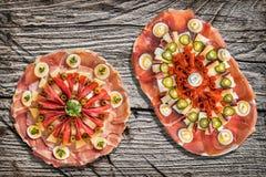 两个传统开胃菜美味盘Meze和在土气老松林野餐桌上设置的被发酵的皮塔小面包干被撕毁的大面包 库存照片