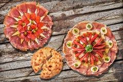 两个传统开胃菜美味盘Meze和在土气老松林野餐桌上设置的被发酵的皮塔小面包干被撕毁的大面包 库存图片