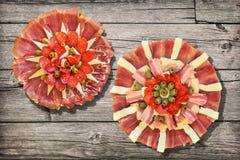 两个传统开胃菜美味盘Meze和在土气老松林野餐桌上设置的被发酵的皮塔小面包干被撕毁的大面包 免版税库存照片