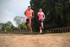 两个体育伙伴在穿橙色和桃红色衬衣的一好日子一起跑步 他们对彼此跳并且微笑 ?? 免版税图库摄影