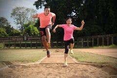 两个体育伙伴在穿橙色和桃红色衬衣的一好日子一起跑步 他们看彼此,并且微笑,享用 库存照片