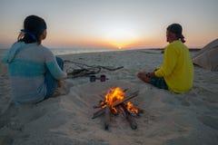 两个作的旅客在灼烧的火旁边坐 免版税库存照片