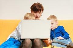 两个使用膝上型计算机的小男孩和母亲 库存图片