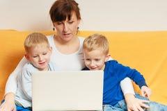 两个使用膝上型计算机的小男孩和母亲 免版税库存照片