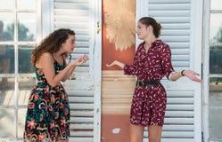两个俏丽的女孩做着意大利语什么是您谈论?标志 免版税图库摄影