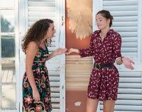两个俏丽的女孩做着意大利语什么是您谈论?标志 免版税库存图片
