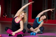 两个俏丽的女孩在健身中心做身体弯曲在席子 库存图片