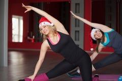 两个俏丽的女孩在圣诞老人帽子做身体弯曲在席子  免版税图库摄影