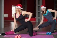 两个俏丽的女孩在圣诞老人帽子在健身的席子行使 免版税库存图片