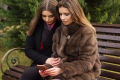 两个俏丽的女孩采取与智能手机的selfie 免版税库存图片