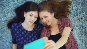 两个俏丽的女孩顶视图在家做selfie画象的睡衣的在床在卧室 股票录像