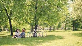 两个俏丽的女朋友谈话,并且笑的坐草坪在公园警告晴天在夏天 骑自行车现代 影视素材