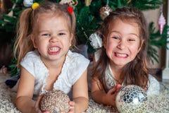 两个俏丽的姐妹在圣诞树旁边笑和显示牙 图库摄影