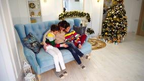 两个儿子和男孩兄弟的愉快的母亲肩并肩和在家庭方式容忍坐在欢乐的蓝色沙发装饰的 股票视频