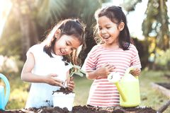 两个儿童亚洲女孩植物幼木年轻人树 图库摄影