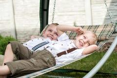 两个兄弟休息并且获得乐趣 孩子在吊床在 免版税库存图片