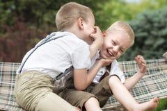 两个兄弟休息,告诉在他的耳朵的秘密 在吊床的男孩乘驾 库存照片
