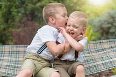 两个兄弟休息,告诉在他的耳朵的秘密 在吊床的男孩乘驾 免版税库存照片