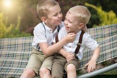 两个兄弟休息,告诉在他的耳朵的秘密 男孩在吊床乘坐 免版税图库摄影