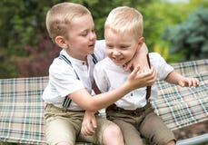 两个兄弟休息,告诉在他的耳朵的秘密 男孩在吊床乘坐 免版税库存照片