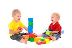两个兄弟修造色的立方体玩具大厦  图库摄影