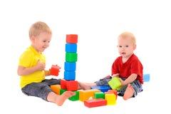 两个兄弟修造色的立方体玩具大厦  库存图片