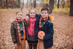 两个兄弟和一个姐妹,三个孩子在森林里 库存照片