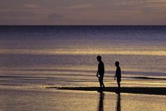 两个兄弟在与五颜六色的海的海滩享用日出的 库存图片