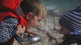 两个兄弟在温暖的衣裳的海滩使用 股票录像