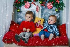 两个兄弟坐新年装饰了窗口 免版税库存照片