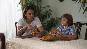 两个兄弟坐谈和吃新月形面包和饮料热奶咖啡的厨房用桌 更老和弟弟 股票视频