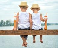 两个兄弟摇摆了他们的从木码头的腿在湖并且喝新鲜的汁液 免版税库存图片