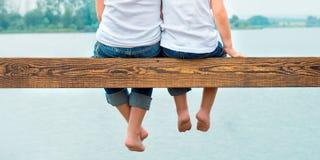 两个兄弟摇摆了他们的从木码头的腿 在湖的家庭度假 免版税库存照片