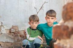 两个兄弟是孤儿,掩藏在一个被放弃的房子,吓唬由灾害和敌意 提议照片 库存图片