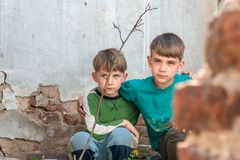 两个兄弟是孤儿,掩藏在一个被放弃的房子,吓唬由灾害和敌意 提议照片 免版税库存图片