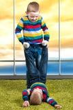 两个兄弟演奏,获得乐趣,交朋友 在同样衣裳打扮的孩子 免版税图库摄影