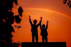 两个兄弟用他们的手在日落的彩虹下在夏天 库存照片