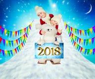 两个兄弟,与一头北极熊一起,从山滑雪 圣诞快乐和节日快乐! 免版税图库摄影