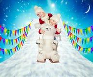 两个兄弟,与一头北极熊一起,从山滑雪 新年2018年 圣诞快乐和节日快乐! 库存照片